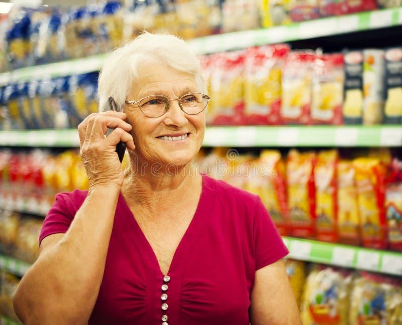 Ανώτερη γυναίκα στο κατάστημα παντοπωλείων στοκ φωτογραφία