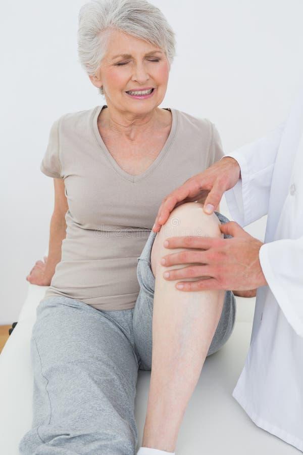 Ανώτερη γυναίκα Displeased που παίρνει το γόνατό της εξετασμένο στοκ φωτογραφία