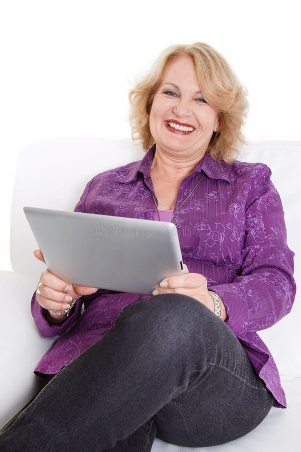Ανώτερη γυναικεία ανάγνωση eBook στοκ εικόνες