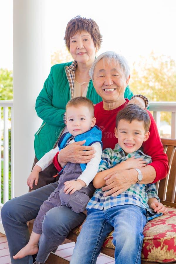 Ανώτερη ενήλικη κινεζική συνεδρίαση ζεύγους με τη μικτή φυλή τους Grandc στοκ φωτογραφίες με δικαίωμα ελεύθερης χρήσης