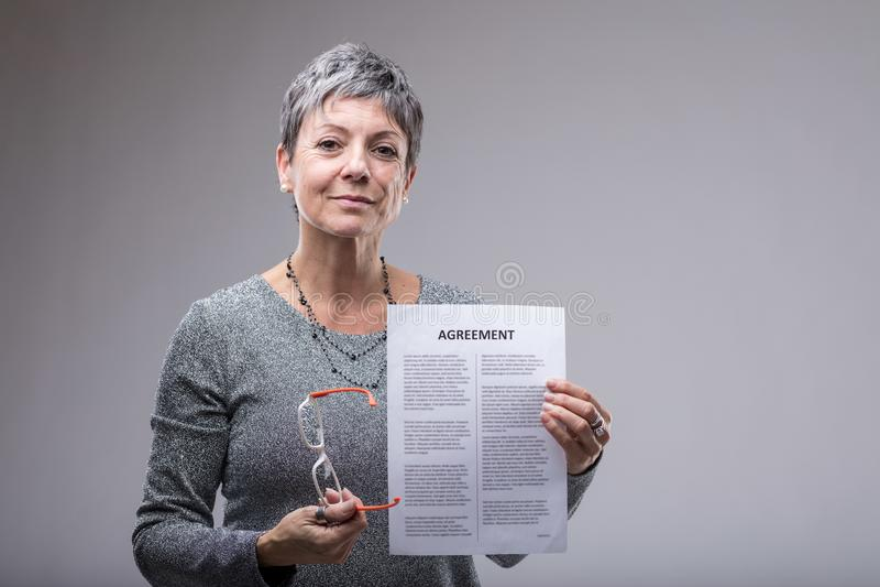 Ανώτερη επιχειρηματίας που κρατά ψηλά μια δακτυλογραφημένη συμφωνία στοκ φωτογραφία με δικαίωμα ελεύθερης χρήσης