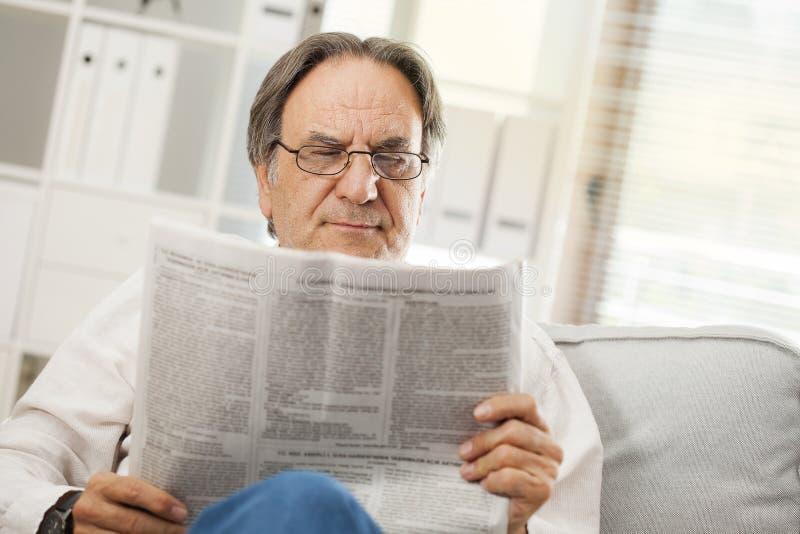 Ανώτερη εφημερίδα ανάγνωσης ατόμων στο σπίτι στοκ φωτογραφία