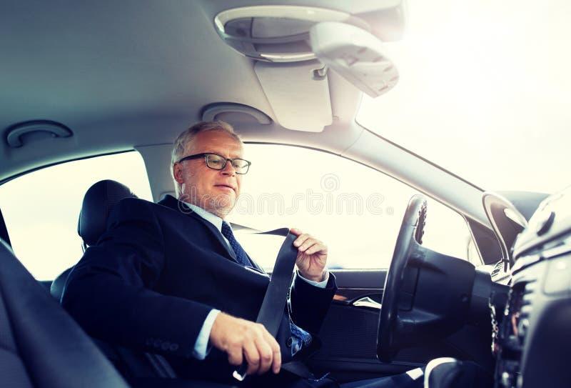 Ανώτερη ζώνη ασφαλείας αυτοκινήτων επιχειρηματιών στερεώνοντας στοκ φωτογραφία