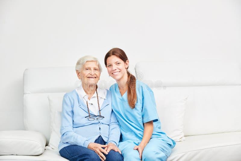 Ανώτερη και θηλυκή γηριατρική νοσοκόμα στον καναπέ στοκ φωτογραφία με δικαίωμα ελεύθερης χρήσης
