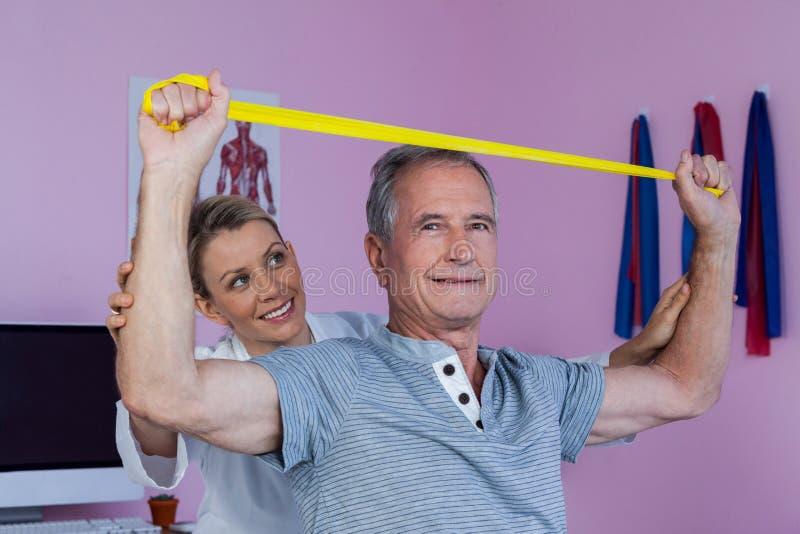 Ανώτερη κατάρτιση ατόμων με τη ζώνη άσκησης που βοηθιέται από το φυσιοθεραπευτή στοκ φωτογραφίες με δικαίωμα ελεύθερης χρήσης