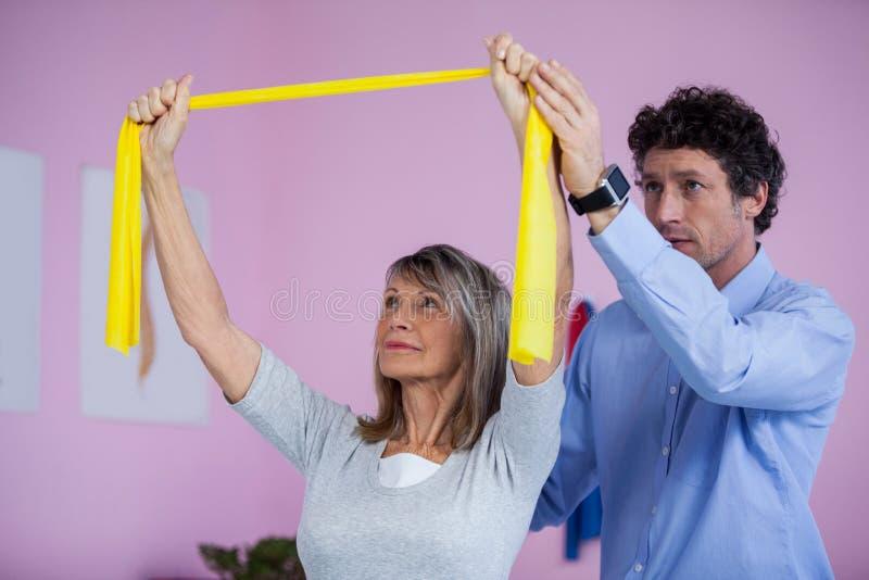 Ανώτερη κατάρτιση γυναικών με τη ζώνη άσκησης που βοηθιέται από το φυσιοθεραπευτή στοκ εικόνα