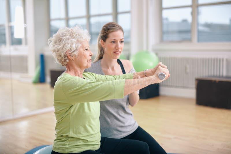 Ανώτερη κατάρτιση γυναικών στη γυμναστική με έναν προσωπικό εκπαιδευτή στοκ φωτογραφία