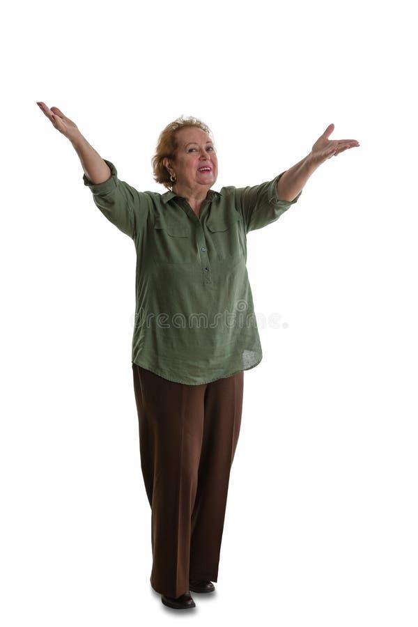 Ανώτερη κυρία που στέκεται με το χαιρετισμό της χειρονομίας στοκ εικόνες