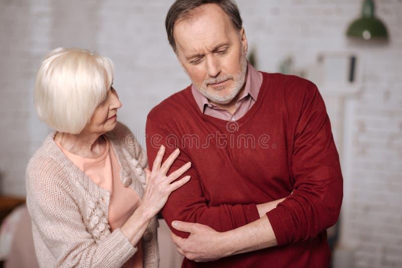 Ανώτερη κυρία που φροντίζει το σύζυγο με το στομαχόπονο στοκ φωτογραφίες με δικαίωμα ελεύθερης χρήσης