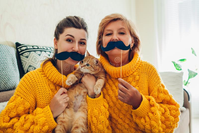 Ανώτερη μητέρα και η ενήλικη κόρη της που παίρνουν selfie με τη γάτα χρησιμοποιώντας τα στηρίγματα θαλάμων φωτογραφιών στο σπίτι  στοκ εικόνες