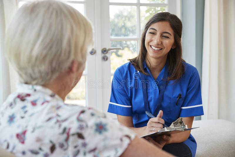 Ανώτερη νοσοκόμα συνεδρίασης γυναικών στο σπίτι με προσοχή που παίρνει τις σημειώσεις στοκ εικόνες