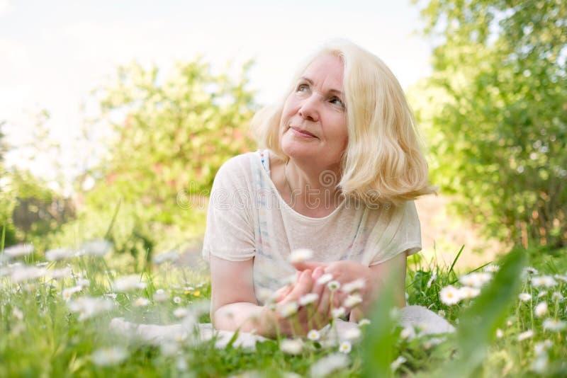Ανώτερη ξανθή γυναίκα που στηρίζεται στη χλόη το καλοκαίρι στοκ εικόνα