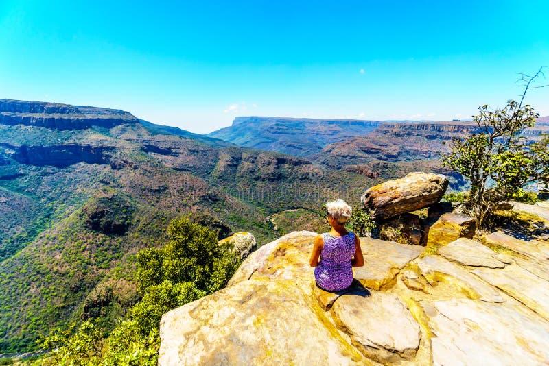 Ανώτερη συνεδρίαση γυναικών σε μια άκρη απότομων βράχων ` s, που απολαμβάνει τη θέα του φαραγγιού ποταμών Blyde από την άποψη στα στοκ φωτογραφία