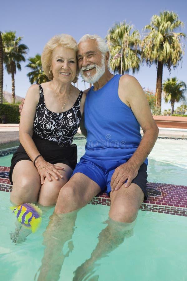 Ανώτερη συνεδρίαση ζεύγους στην πισίνα στοκ φωτογραφία