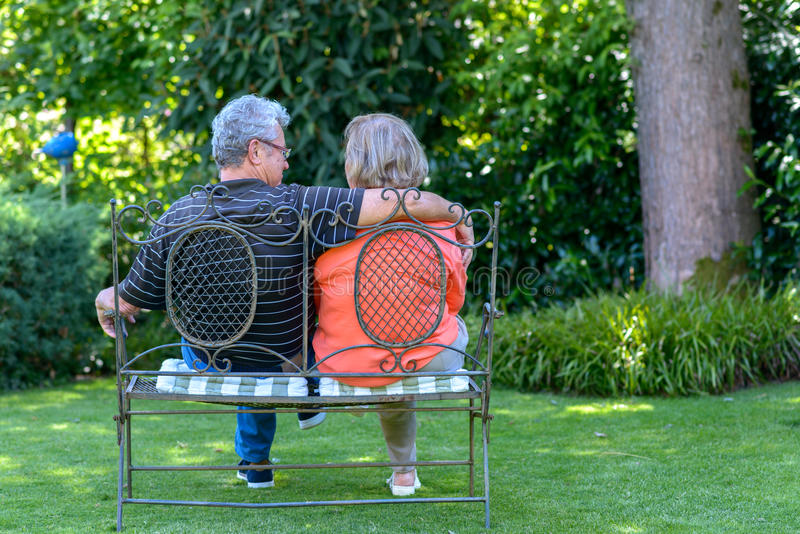 Ανώτερη συνεδρίαση ζευγών στον πάγκο στον κήπο στοκ φωτογραφίες