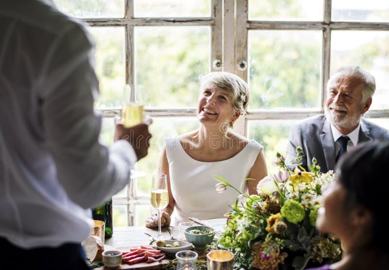 Ανώτερη συνεδρίαση ζεύγους εύθυμη στη δεξίωση γάμου στοκ φωτογραφία
