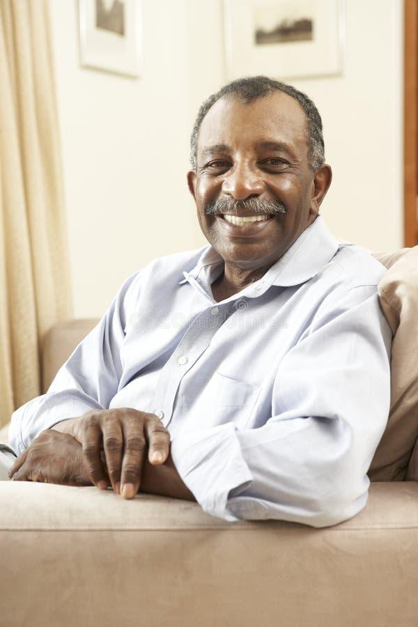 Ανώτερη χαλάρωση ατόμων στην έδρα στο σπίτι στοκ εικόνες