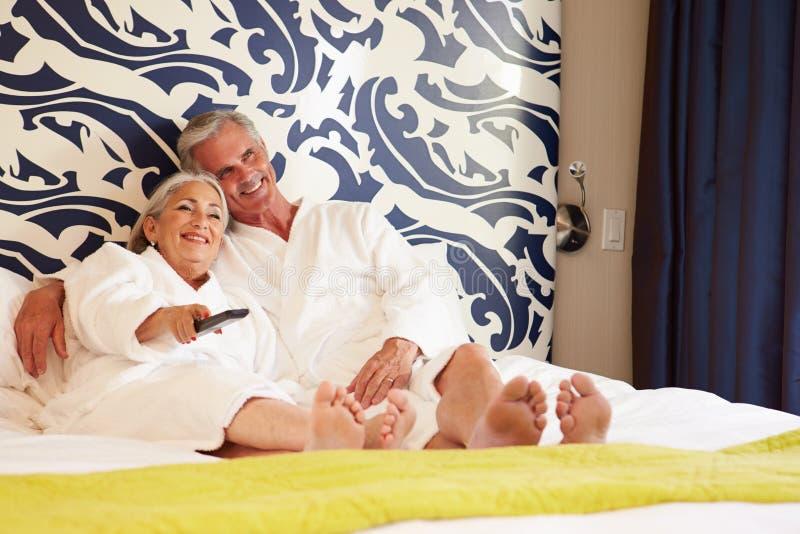 Ανώτερη χαλάρωση ζεύγους στην τηλεόραση προσοχής δωματίου ξενοδοχείου στοκ φωτογραφία με δικαίωμα ελεύθερης χρήσης