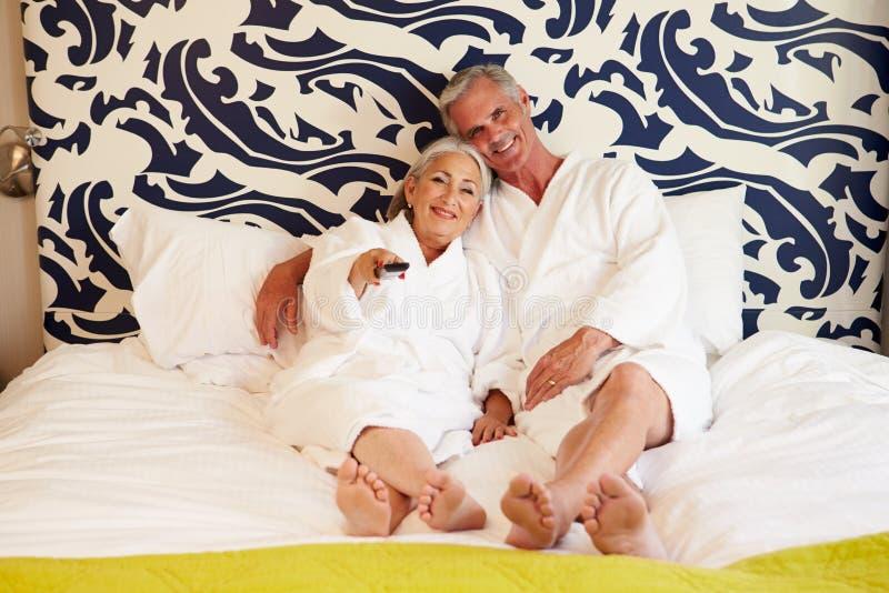 Ανώτερη χαλάρωση ζεύγους στην τηλεόραση προσοχής δωματίου ξενοδοχείου στοκ εικόνα