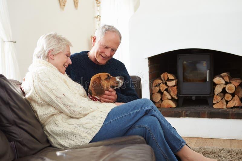 Ανώτερη χαλάρωση ζεύγους στο σπίτι με το σκυλί της Pet στοκ φωτογραφία με δικαίωμα ελεύθερης χρήσης