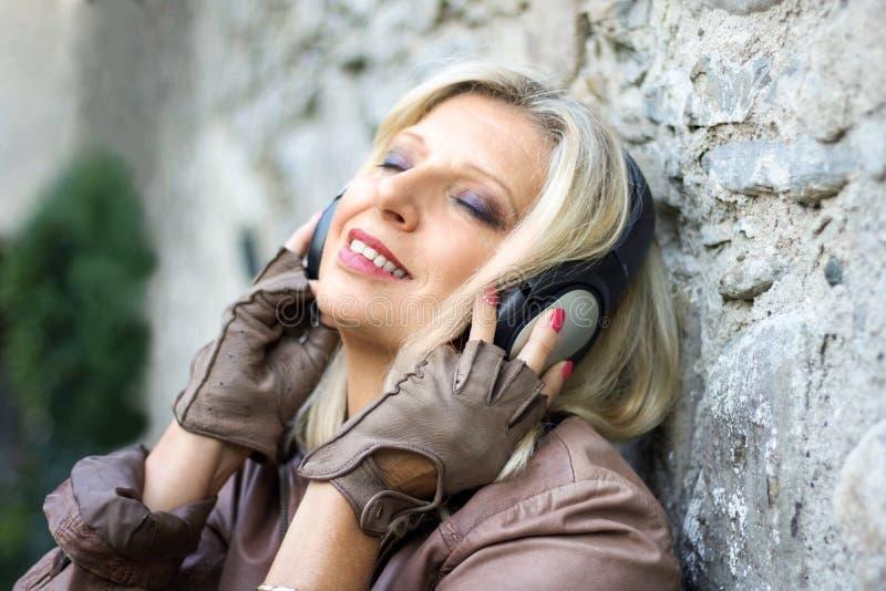 Ανώτερη όμορφη γυναίκα κοντά σε έναν τοίχο πετρών με το ακουστικό στοκ φωτογραφία με δικαίωμα ελεύθερης χρήσης