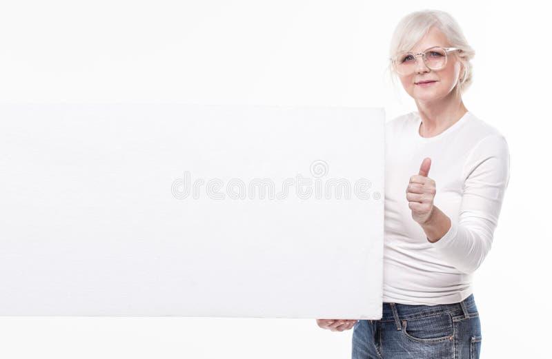 Ανώτερη όμορφη γυναίκα με τον κενό λευκό πίνακα στοκ φωτογραφίες