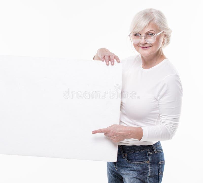 Ανώτερη όμορφη γυναίκα με τον κενό λευκό πίνακα στοκ εικόνες