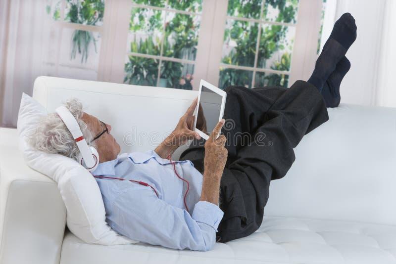 Ανώτερη lenjoying μουσική ατόμων με τα ακουστικά στοκ εικόνα με δικαίωμα ελεύθερης χρήσης