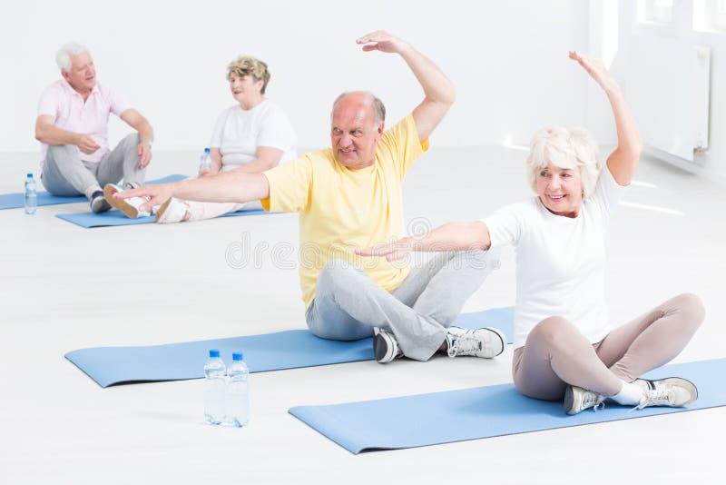 Ανώτεροι άνθρωποι που κάνουν τις ασκήσεις γιόγκας στοκ εικόνα