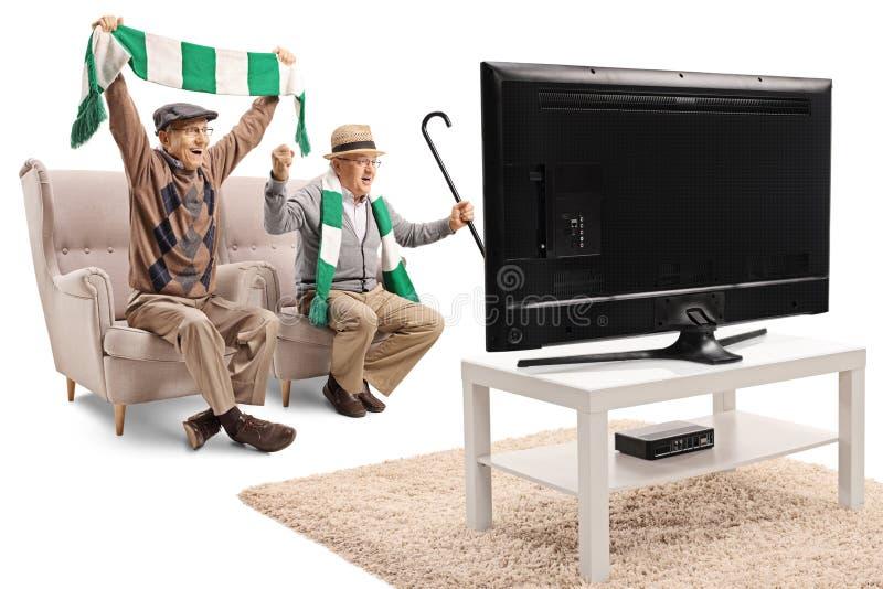 Ανώτεροι αρσενικοί ανεμιστήρες ποδοσφαίρου ενθαρρυντικοί με ένα μαντίλι και προσοχή ενός παιχνιδιού στη TV στοκ φωτογραφία με δικαίωμα ελεύθερης χρήσης