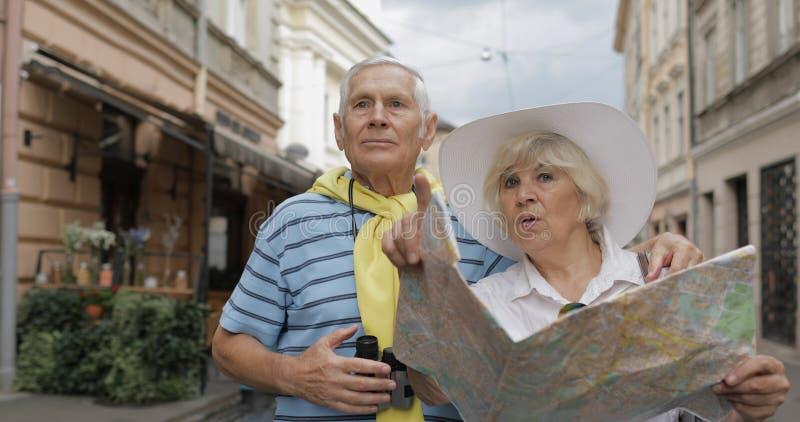 Ανώτεροι αρσενικοί και θηλυκοί τουρίστες που στέκονται με έναν χάρτη στα χέρια που ψάχνουν τη διαδρομή στοκ εικόνες