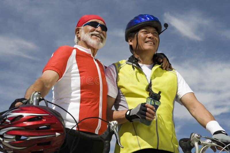 Ανώτεροι αρσενικοί ποδηλάτες που στέκονται ενάντια στον ουρανό στοκ εικόνες με δικαίωμα ελεύθερης χρήσης