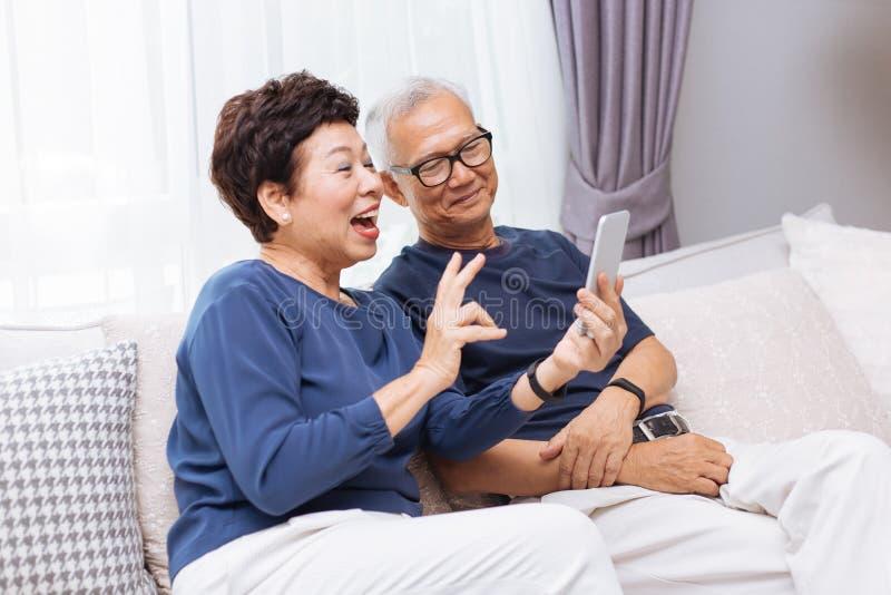 Ανώτεροι ασιατικοί παππούδες και γιαγιάδες ζευγών που κάνουν ένα βίντεο να καλέσει και που κυματίζουν στον επισκέπτη στοκ εικόνα