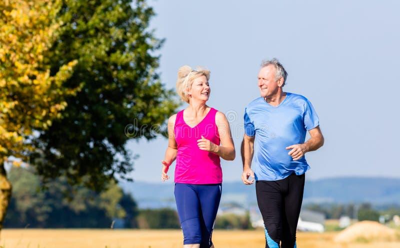 Ανώτεροι γυναίκα και άνδρας που τρέχουν κάνοντας τις ασκήσεις ικανότητας στοκ φωτογραφίες