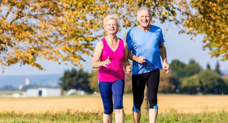 Ανώτεροι γυναίκα και άνδρας που τρέχουν κάνοντας τις ασκήσεις ικανότητας στοκ φωτογραφία