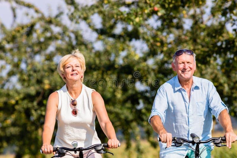 Ανώτεροι γυναίκα και άνδρας στο γύρο ποδηλάτων στοκ εικόνες