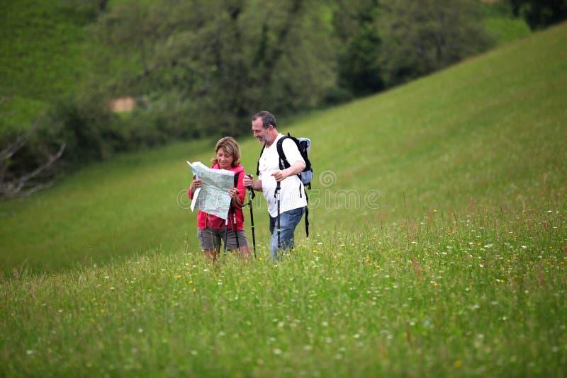 Ανώτεροι οδοιπόροι που εξετάζουν το χάρτη που στέκεται στο λιβάδι στοκ εικόνες