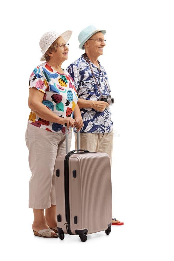 Ανώτεροι τουρίστες με μια βαλίτσα που περιμένει στη γραμμή στοκ εικόνες