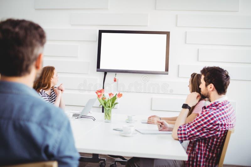 Ανώτεροι υπάλληλοι που προσέχουν στην τηλεόραση στο δημιουργικό γραφείο στοκ εικόνες