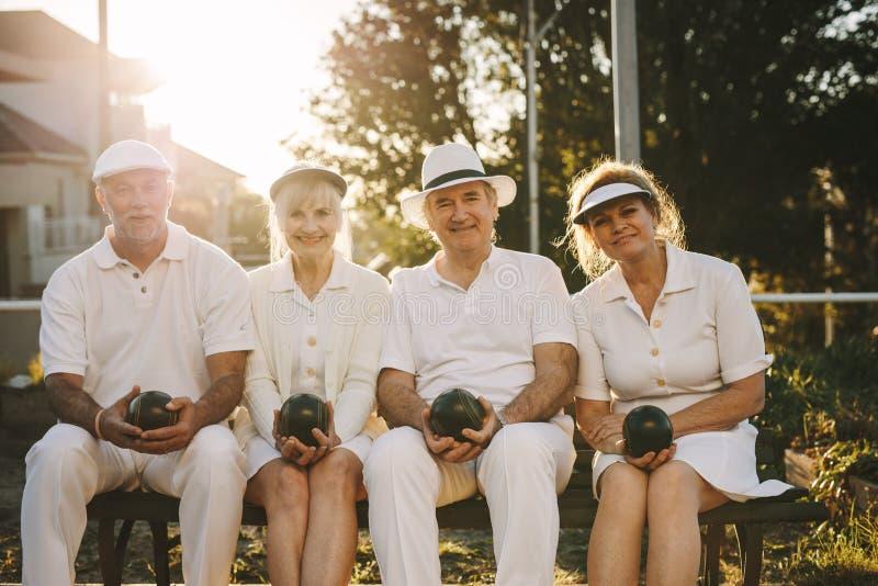 Ανώτεροι φίλοι που κάθονται υπαίθρια με τα boules διαθέσιμα στοκ εικόνες με δικαίωμα ελεύθερης χρήσης