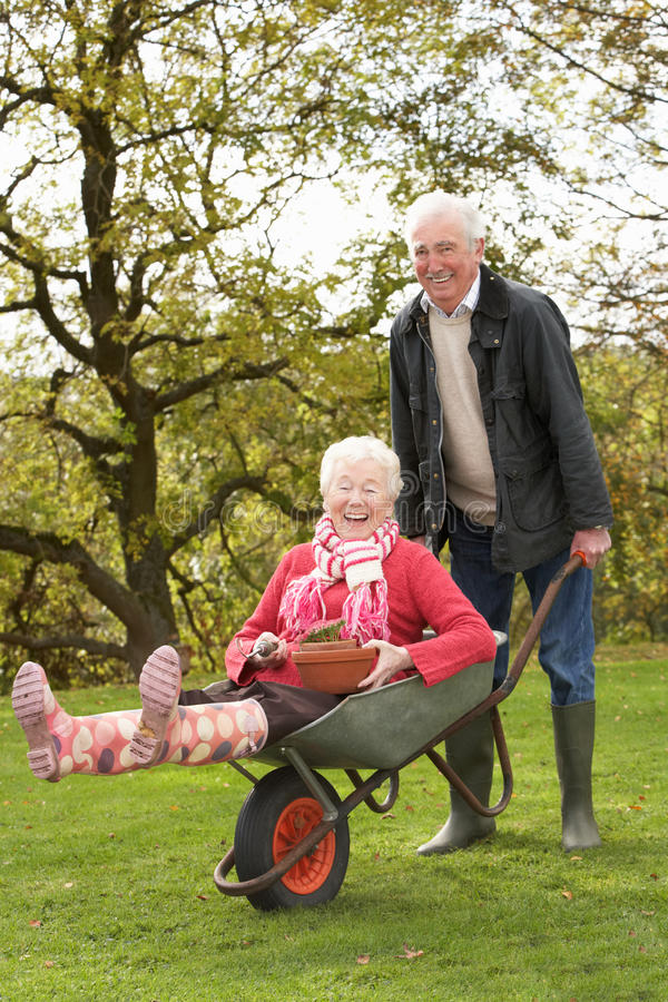 Ανώτερος άνδρας ζεύγους που δίνει το γύρο γυναικών Wheelbarrow στοκ φωτογραφία