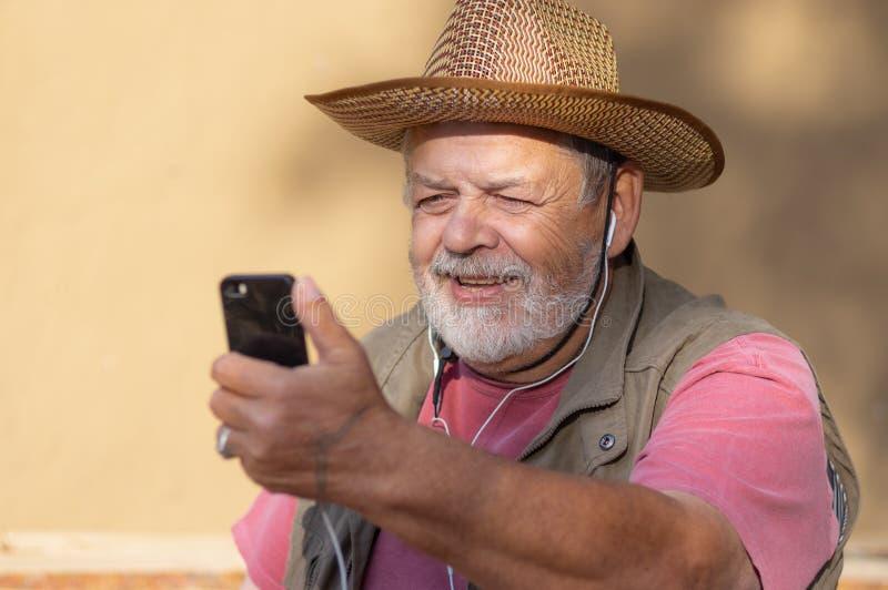 Ανώτερος άνδρας με άχυρο που ακούει μουσική από κινητό πάνω από ακουστικά, ενώ κάθεται σε εξωτερικό χώρο ενάντια στον πηλό τοίχο στοκ εικόνες με δικαίωμα ελεύθερης χρήσης