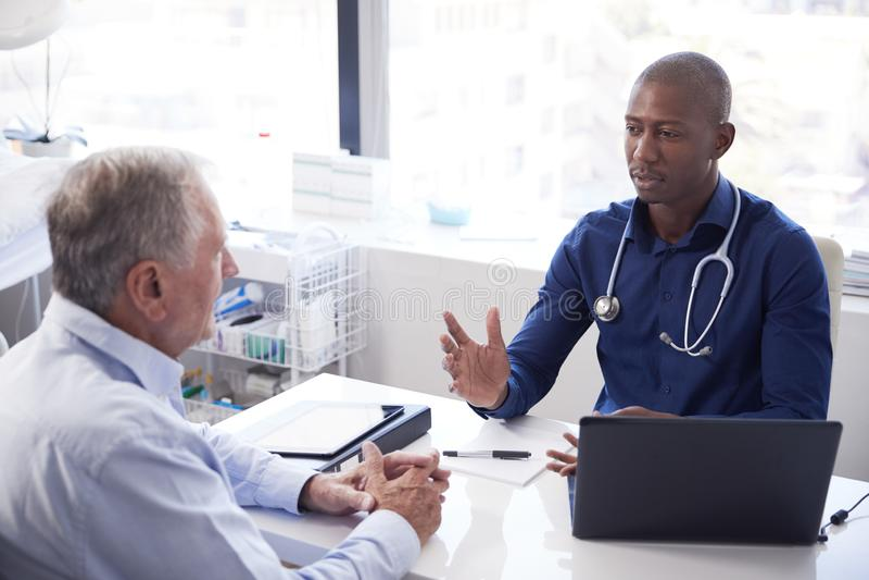 Ανώτερος αρσενικός ασθενής κατόπιν διαβουλεύσεων με τη συνεδρίαση γιατρών στο γραφείο στην αρχή στοκ φωτογραφίες
