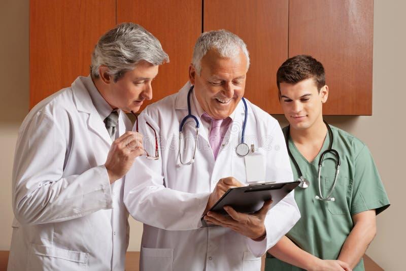 Ανώτερος αρσενικός γιατρός με τους συναδέλφους στοκ εικόνα