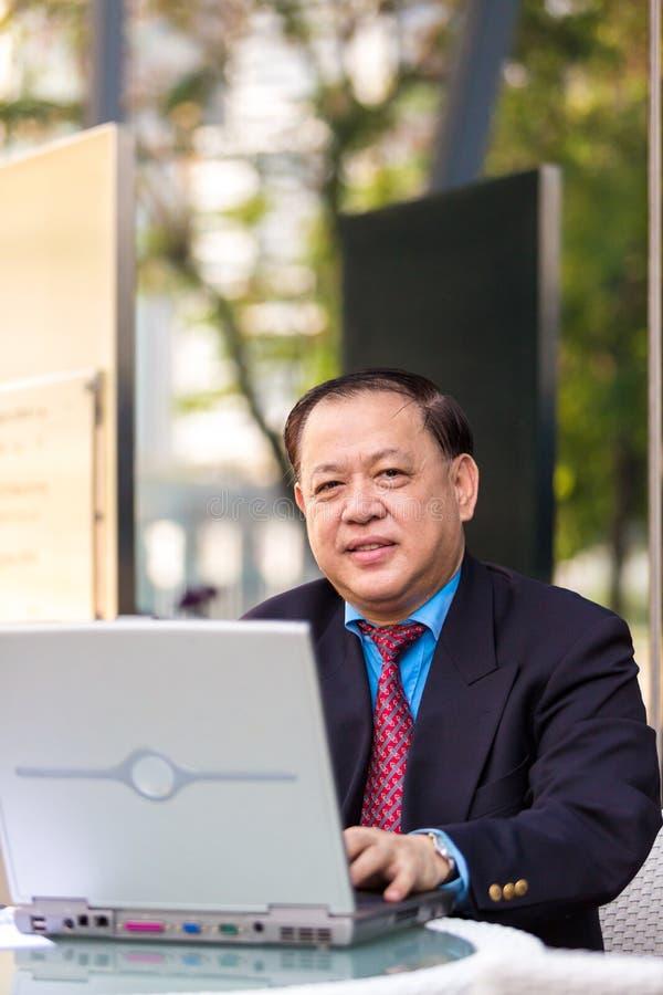Ανώτερος ασιατικός επιχειρηματίας στο κοστούμι που χρησιμοποιεί το PC lap-top στοκ φωτογραφίες