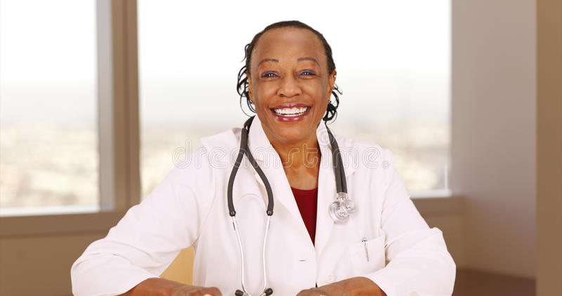 Ανώτερος αφρικανικός γιατρός που χαμογελά στη κάμερα στοκ εικόνες