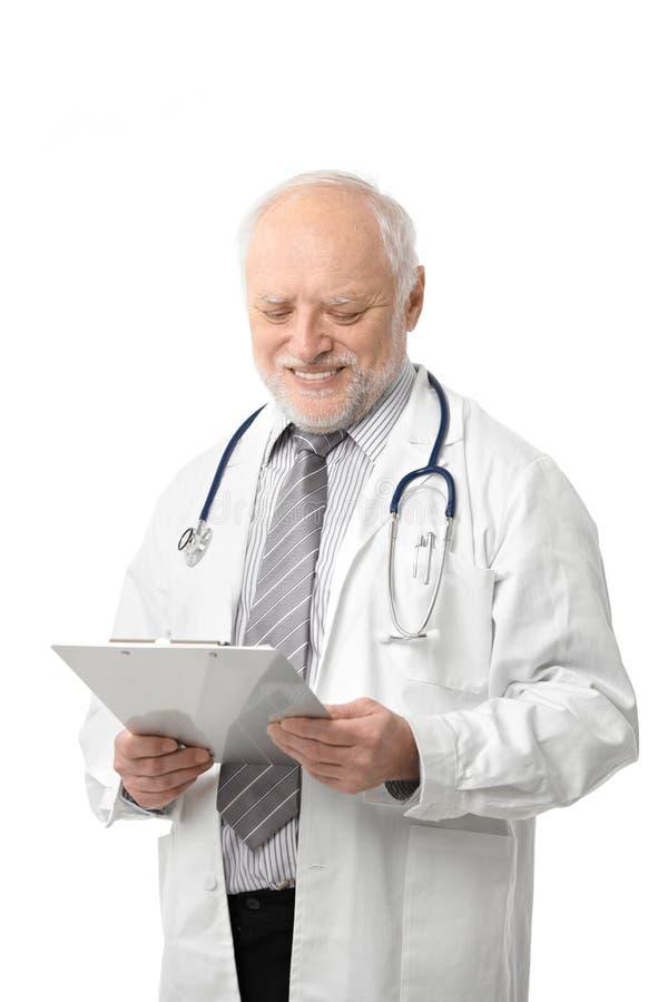 Ανώτερος γιατρός που εξετάζει το χαμόγελο εγγράφων στοκ εικόνες