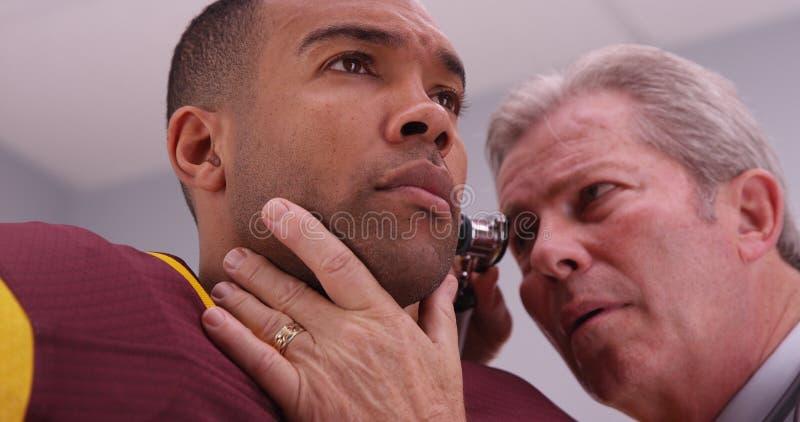 Ανώτερος γιατρός που ελέγχει το αυτί του αθλητικού αθλητή με ένα ωτοσκόπιο στοκ φωτογραφία με δικαίωμα ελεύθερης χρήσης