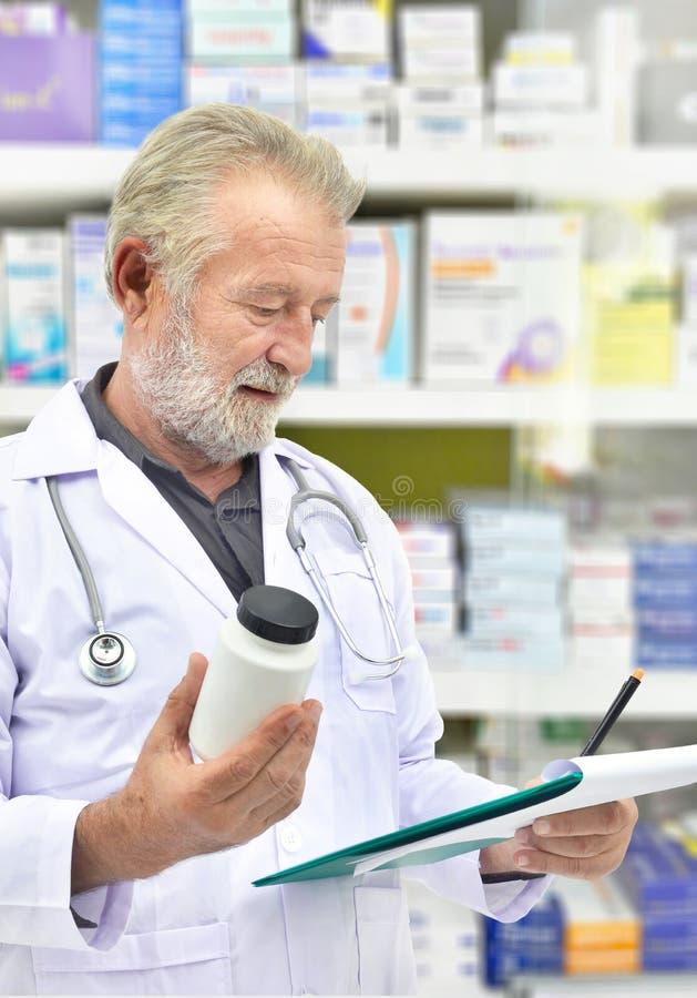Ανώτερος γιατρός που φαίνεται μπουκάλι ιατρικής και υπομονετικό διάγραμμα στο υπόβαθρο ραφιών ιατρικής στοκ εικόνα με δικαίωμα ελεύθερης χρήσης