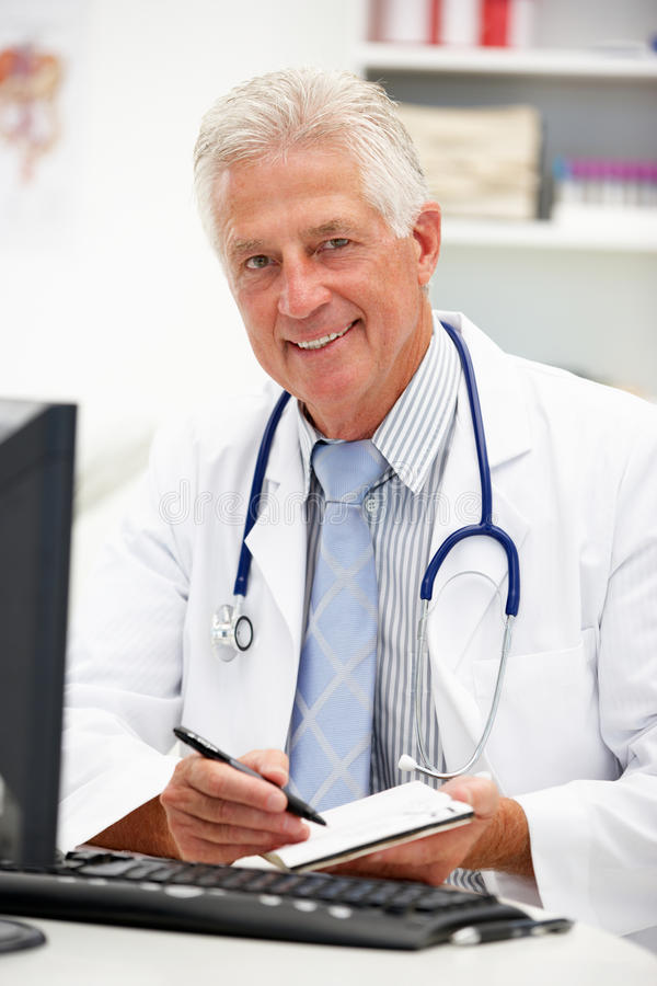 Ανώτερος γιατρός στο γραφείο που παίρνει τις σημειώσεις στοκ εικόνα με δικαίωμα ελεύθερης χρήσης
